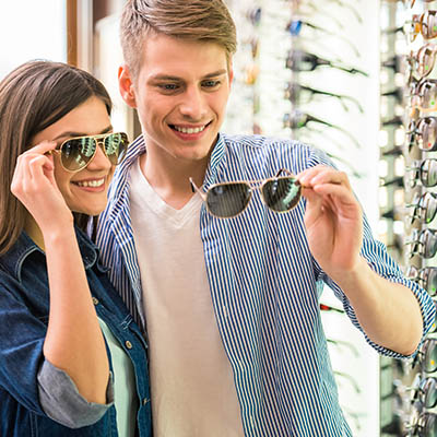 Young couple at optician in the store, they looking for glasses.